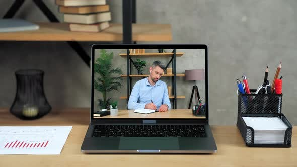 Laptop Standing on Table Display with Businessman in Office Writes in Notebook