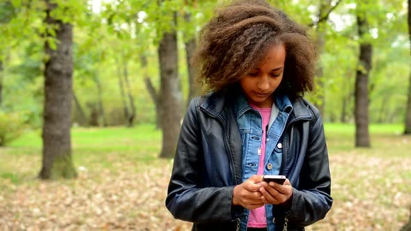 Thumbnail for Young African Friendly Girl Write Messages on the Smartphone and Think What Could She Write