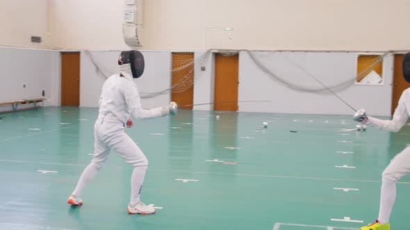 Thumbnail for Two Young Women in Full Protection of White Suits Having an Active Fencing Training in the School