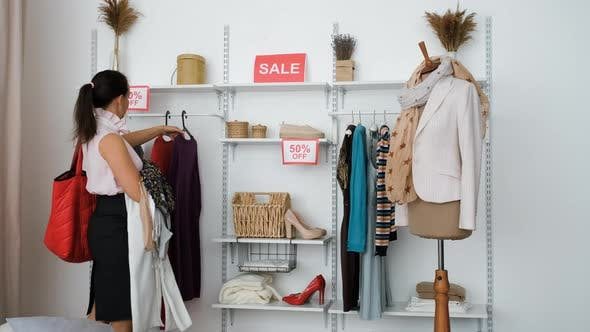 Shopaholic Woman Grabbing Lot of Clothes on Sale