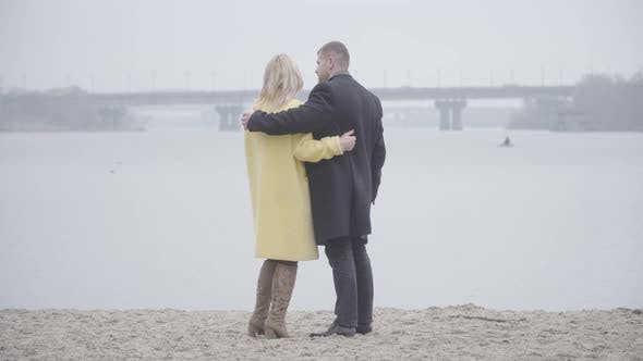 Thumbnail for Wide Shot of Loving Adult Couple Standing on Riverbank and Talking
