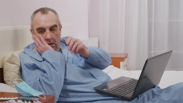 An Elderly Man Watches the News and Puts on a Protective Mask in Panic. Concept of Fear, Panic.