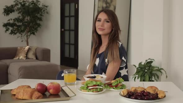 Thumbnail for Beautiful Young Woman Sitting on Table with Appetizing Tasty Breakfast Medium Shot