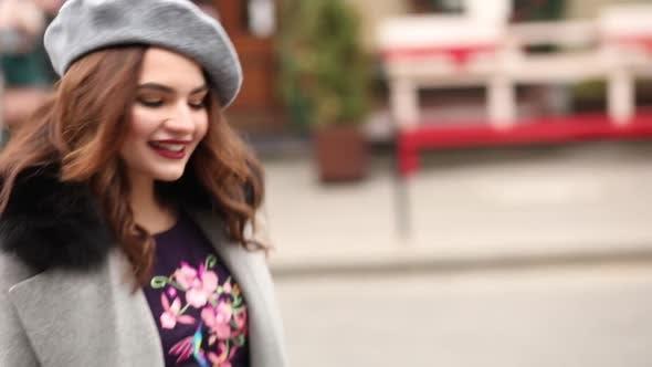 Thumbnail for Beautiful Girl in Grey Coat and Beret Walking Towards Christmas Shops.