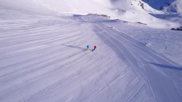 Aerial drone view of a man and woman couple skiing in the snow at a ski resort