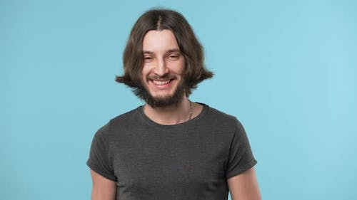 Portrait of Young Hairy Man 20s Wearing Casual Gray Tshirt and Necklace Smiling Broadly in Good Mood