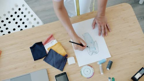 Closeup of Female Designer's Hands Drawing Sketches of New Trendy Clothes on Paper on Table