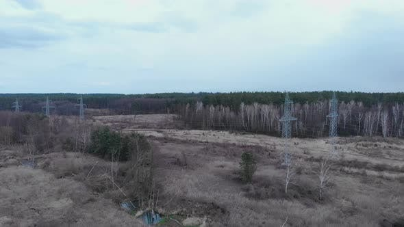 Electric high voltage pylons in forest. Transmission towers. Electricity pylons.