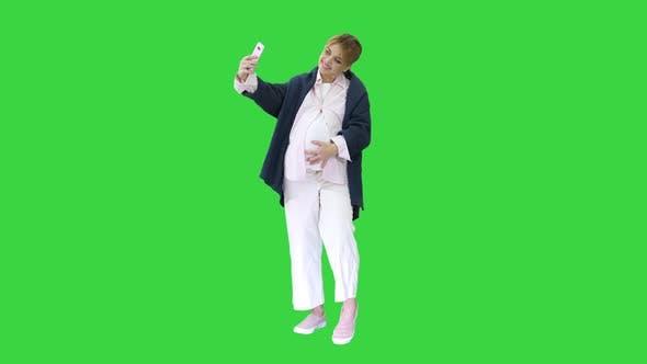 Thumbnail for Glückliche junge schwangere Frau nimmt Selfie auf einem grünen Bildschirm, Chroma Key.