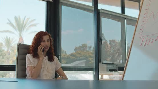 Thumbnail for A business woman with ginger hair talking on the phone while sitting in her office. Slow motion.