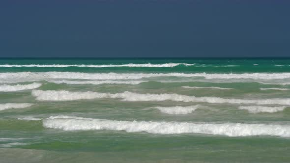 Cover Image for Ocean Waves Breaking and Forming White Foam Over Blue Sky