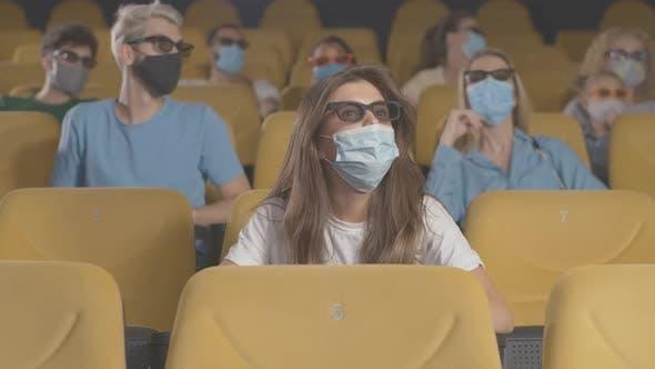 Thumbnail for Menschen in Gesichtsmasken beobachten 3D Film im Kino auf Coronavirus Quarantäne. Film-Liebhaber in 3D -Brille