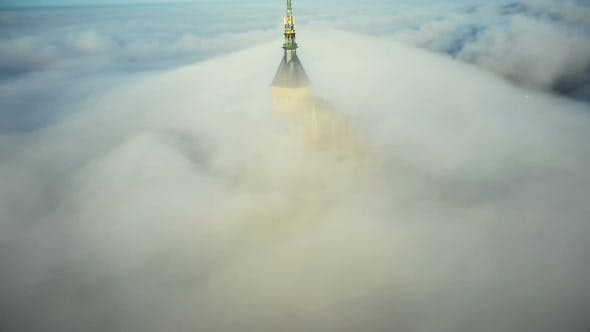 Drone Is Slowly Flying Far Away From Epic Mont Saint Michel Castle Covered By Ethereal Fog Clouds in