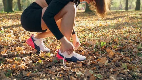 Young Woman Tying Laces on Sport Sneakers at Park