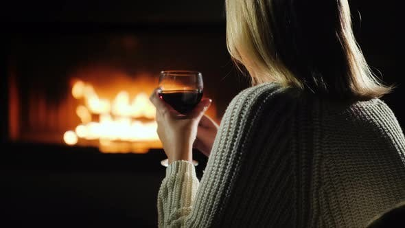 Thumbnail for Woman Drinking Red Wine While Sitting by The Fireplace, Rear View