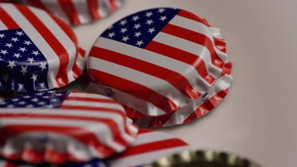 Rotating shot of bottle caps with the American flag printed on them