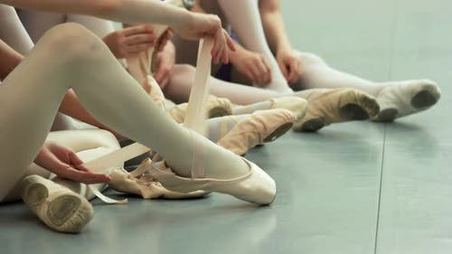 Little Ballerinas Putting on Shoes Close Up