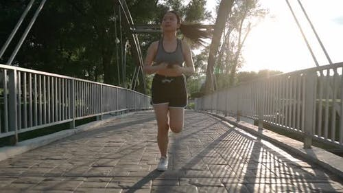 Young Asian Jogger Having a Morning Run Jogging Down the Track in Summer Park Healthy Way of Life