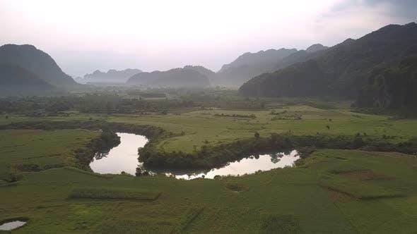Thumbnail for Green Vast Field Near Calm River Reflecting Yellow Sun Rays
