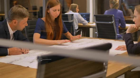Thumbnail for In the Modern Office Three Staff at the Table Look the Drawing Paper and Talking