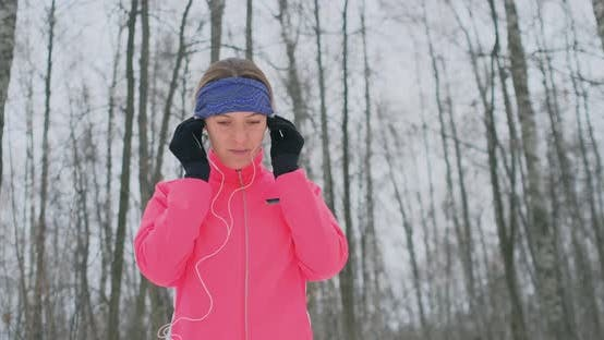 Thumbnail for The Woman Before the Morning Winter Jog Inserts Headphones in the Ears and Is Preparing To Run
