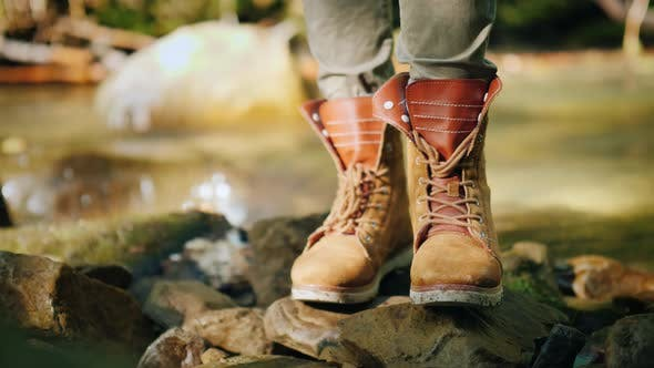 Thumbnail for A Tourist in Trekking Boots Stands Near a Mountain Stream. Hiking and Active Rest
