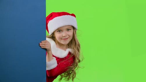 Kid Girl Peeking Out From Behind the Blue Board. Green Screen