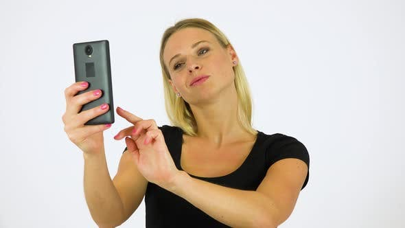 Thumbnail for A Young Beautiful Woman Takes Selfies with a Smartphone - White Screen Studio