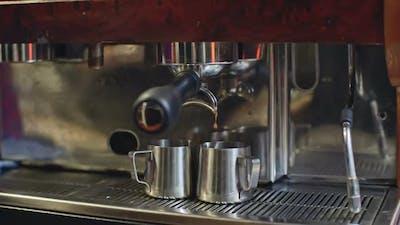 Fresh Espresso Dripping Into Pitchers