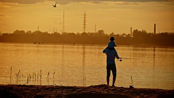 Thumbnail for A Father and His Son on Fishing Together - the Boy Sitting on His Father Shoulders - Sunset