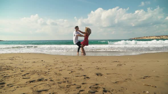 Thumbnail for Young Man and Woman Run Towards Each Other on the Beach
