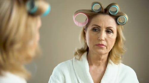 Aged Sad Woman With Hair Curlers and Make-Up Looking at Mirror Reflection