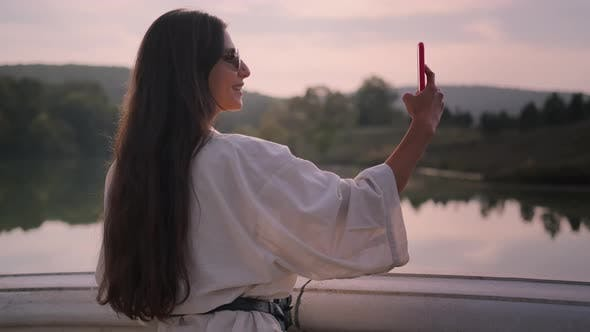 Young Woman is Photographing Nature By Modern Smartphone