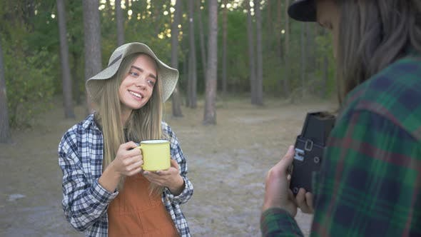 Thumbnail for Young Pretty Caucasian Woman Posing with a Yellow Cup on the Background of Forest. Boyfriend Taking