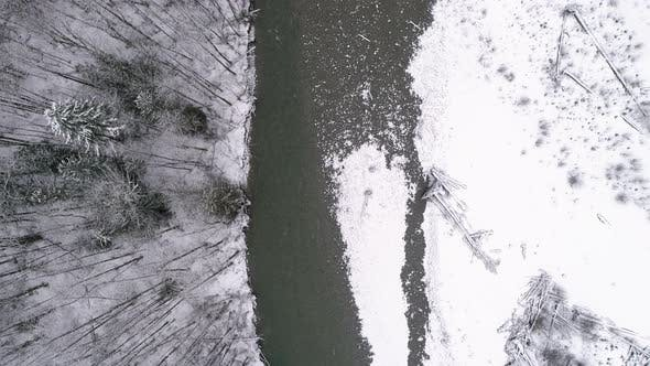 Thumbnail for Birds Eye View Of Ice Cold River Flowing In Snowy Pacific Northwest Mountain Forest