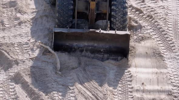 An Old Bulldozer Moves Sand Using a Bucket on Construction Site
