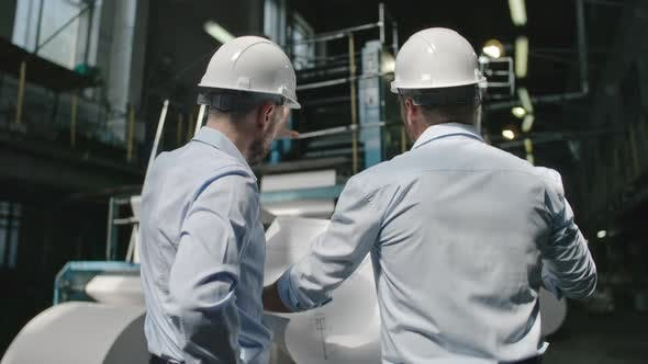 Thumbnail for Engineers Discussing Blueprint in Factory