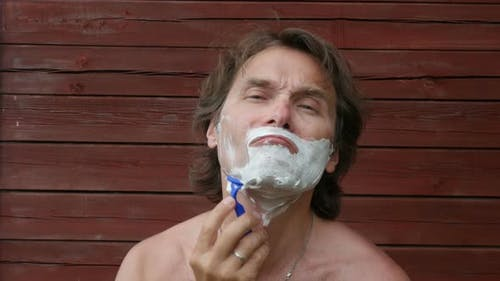 Man Shaving With Blade Shaver Outdoors.
