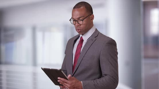 A black executive man does work on his tablet