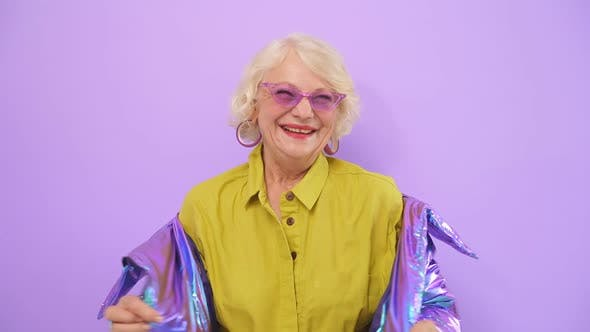 Smiling Cheerful Old Lady Posing for the Camera, Isolated Purple Background