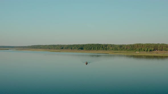 Cover Image for Aerial Drone View of Fisherman on the Boat on the Sunrise, Morning Fishing, Swimming on a Calm Lake