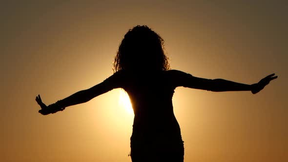 Thumbnail for Girl Dancing Belly Dancing on the Beach Against the Sunset. Silhouettes