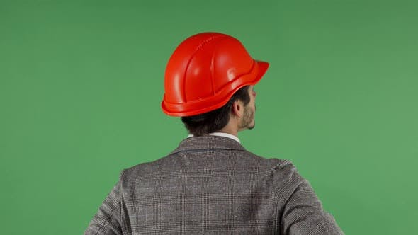 Cover Image for Rear View Portrait of a Contractor Wearing Hardhat Looking at the Green Screen