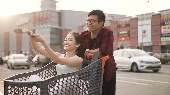 Thumbnail for Smiling Asian Guy Being Pushed in Front of Him Market Trolley with His Cheerful Girlfriend