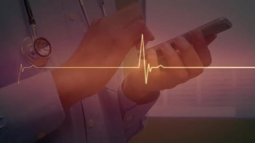 Red glowing heart rate monitor against mid section of male doctor using smartphone