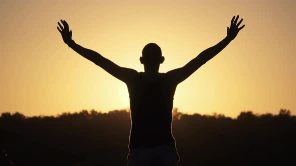 Thumbnail for Silhouette of Young Man Against Sunset Raising Hands Sides and Up. Slow Motion