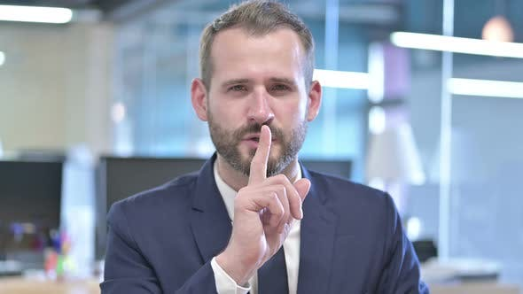 Thumbnail for Portrait of Young Businessman Putting Finger on Lips