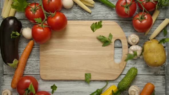 Thumbnail for Parsley Pieces Falling on a Cutting Board with Vegetables Around