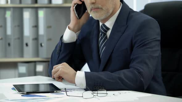 Cover Image for Businessman in Suit Working in Office, Dialing and Talking to Client Over Phone