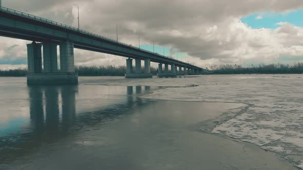 Grey Bridge Over Wide River with Ice Against Dense Forest